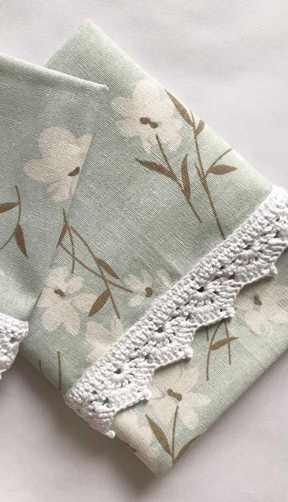 O barrado de crochê em tom cru deixa as flores estampadas no pano de prato ainda mais delicadas