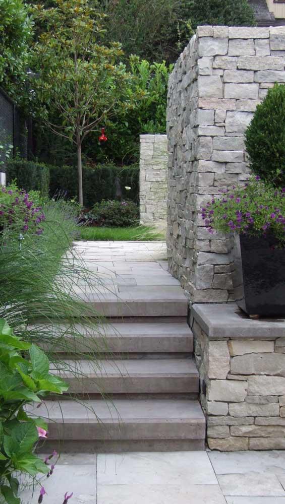 Nessa área externa, a pedra mineira cobre o chão e forma um lindo conjunto com a mureta de pedras brutas
