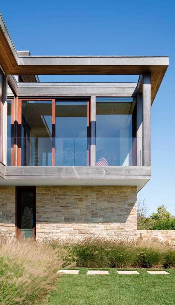 Essa casa moderna ganhou um toque de rusticidade com o uso da pedra mineira nas paredes