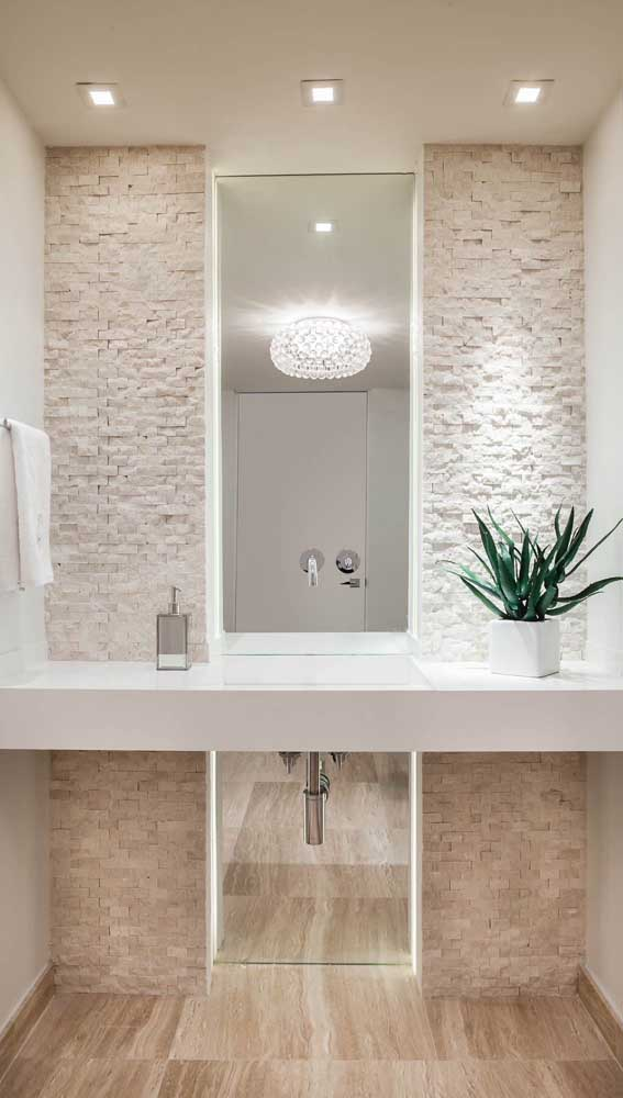 Mosaico de pedra mineira na parede do lavabo. A iluminação valoriza ainda mais o uso das pedras