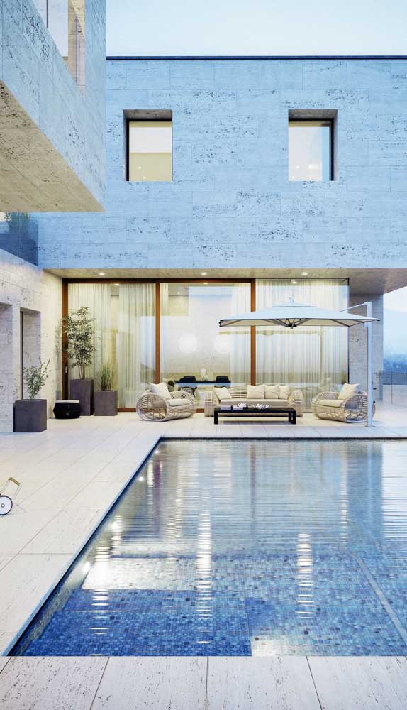 Nessa casa moderna, a pedra mineira reina absoluta nas paredes e no piso
