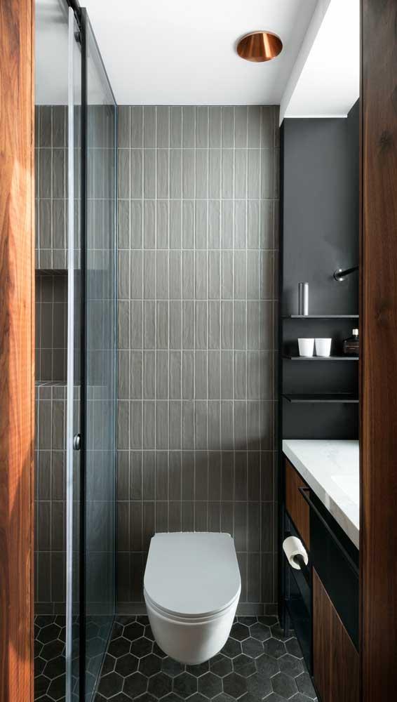 Nesse pequeno banheiro, as prateleiras pretas saem do painel da mesma cor
