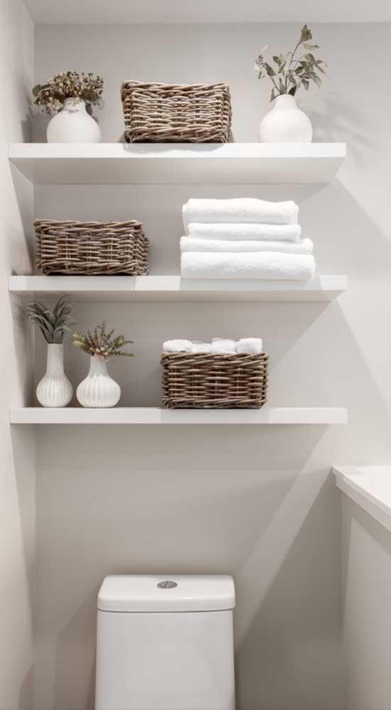 Ideia simples para você tomar como referência: prateleiras brancas suspensas sobre o vaso sanitário