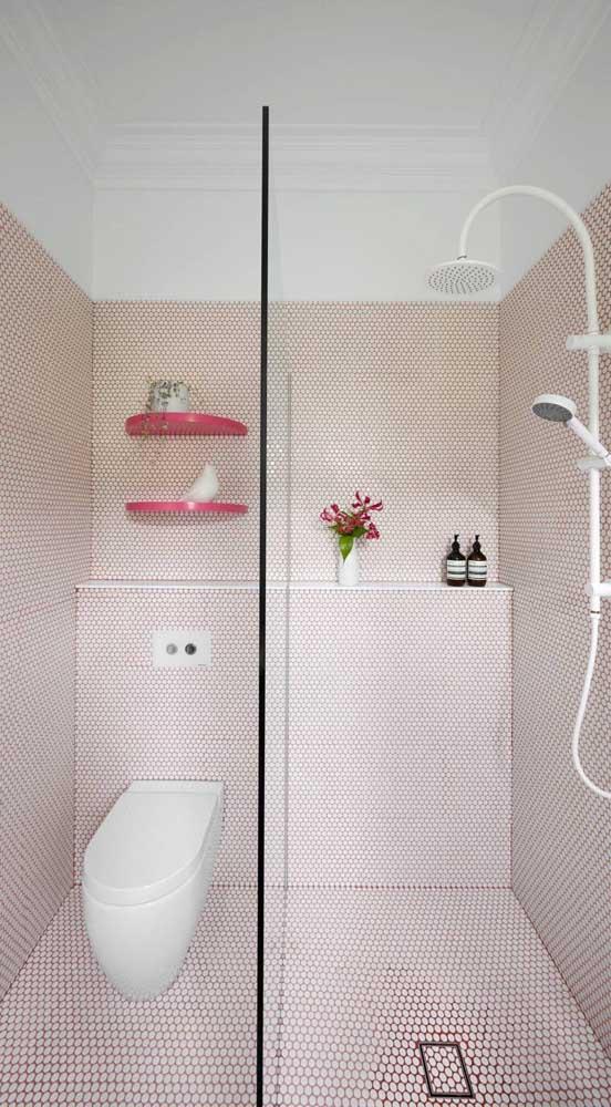 Dividida visualmente pela parede de vidro, a prateleira de alvenaria atende aos dois lados do banheiro