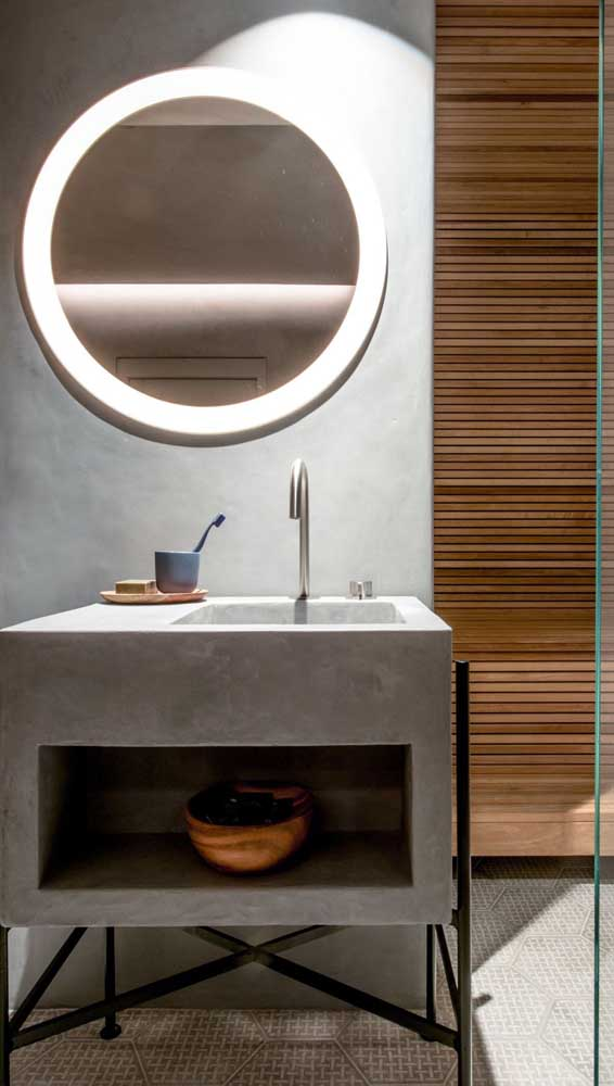 O banheiro de estilo industrial apostou em um armário de concreto com prateleira