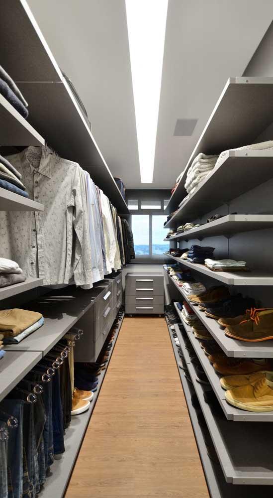 Closet masculino estilo corredor com piso laminado