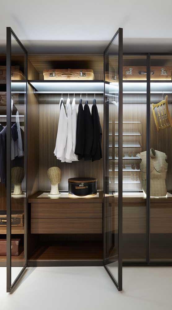 Closet masculino amadeirado com portas de vidro e iluminação embutida