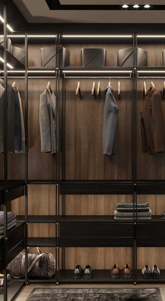 Closet masculino amadeirado e super elegante. As luzes embutidas dão ainda mais charme ao projeto