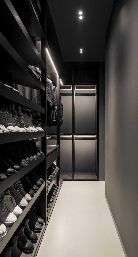 Closet masculino preto com destaque para o espaço grande dedicado somente aos sapatos