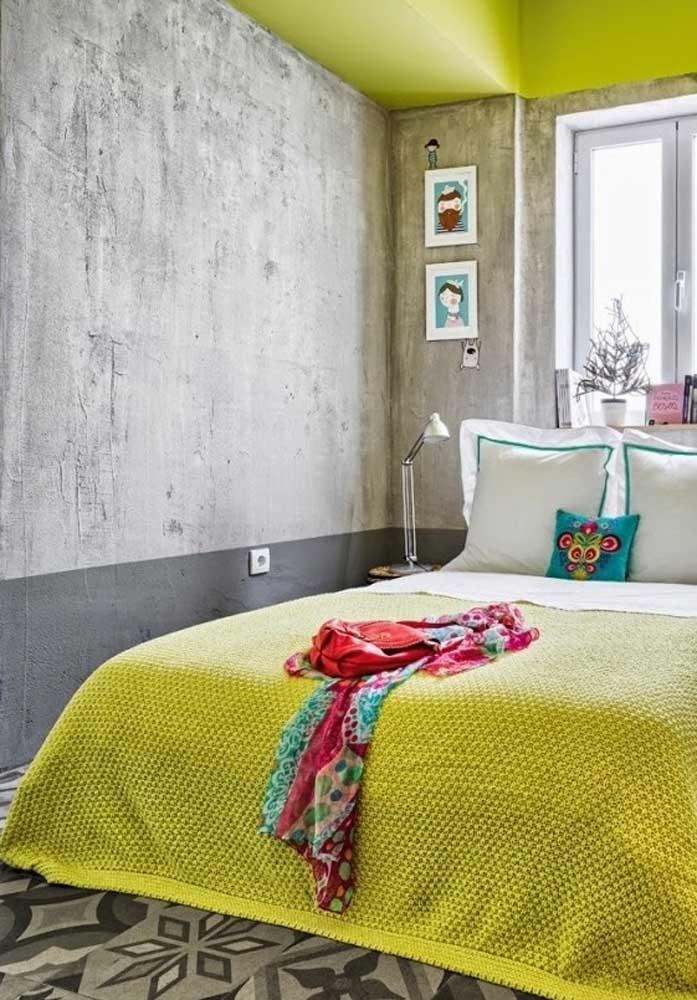 Quer uma decoração mais moderna no seu quarto? Aposte na parede feita com cimento queimado e complemente com a cor amarelo.