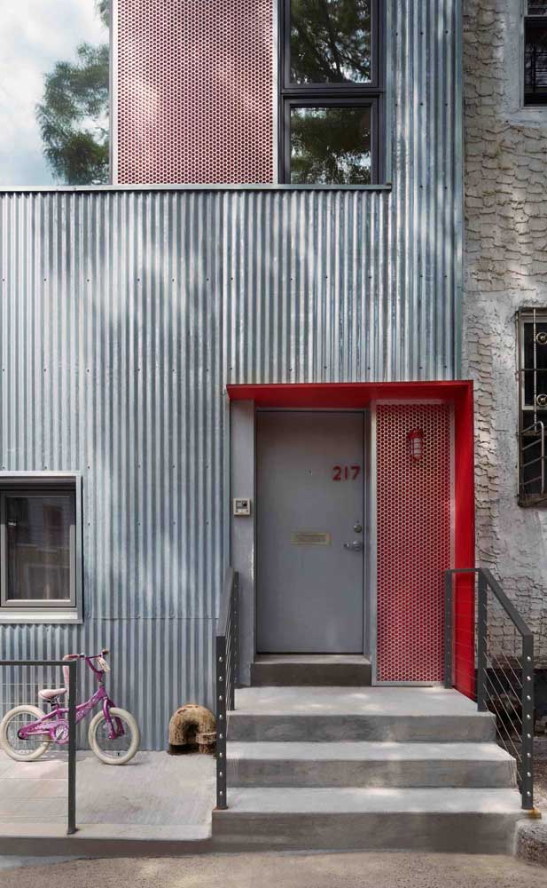 A casa de fachada moderna apostou em uma porta de alumínio de cor natural