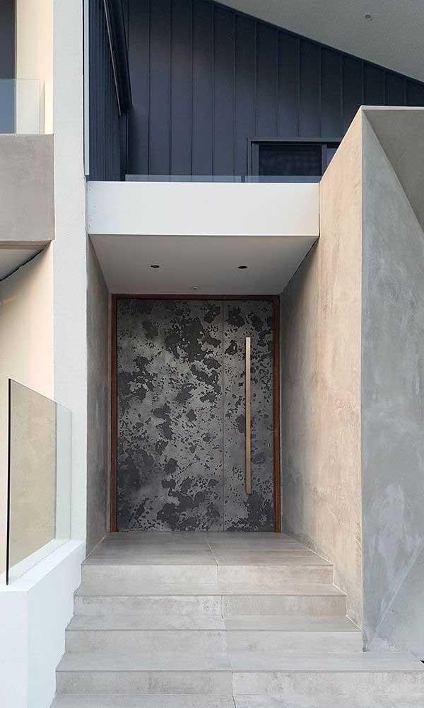 Já nesse projeto, a porta de alumínio se destaca pelas texturas e pelo puxador dourado
