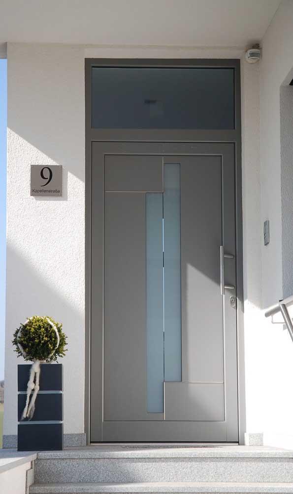 A porta de alumínio cinza traz modernidade para a fachada de estilo clássico