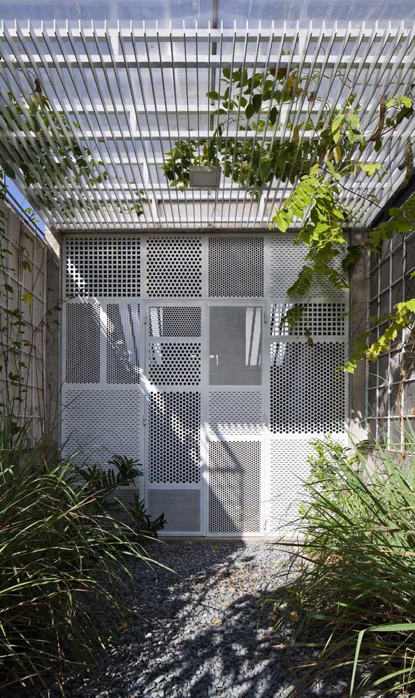 Porta de alumínio com desenhos vazados para delimitar a área do jardim