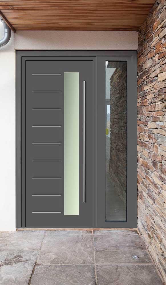 Porta de alumínio pivotante na entrada da casa. Destaque para a pequena abertura em vidro que valoriza o design da porta