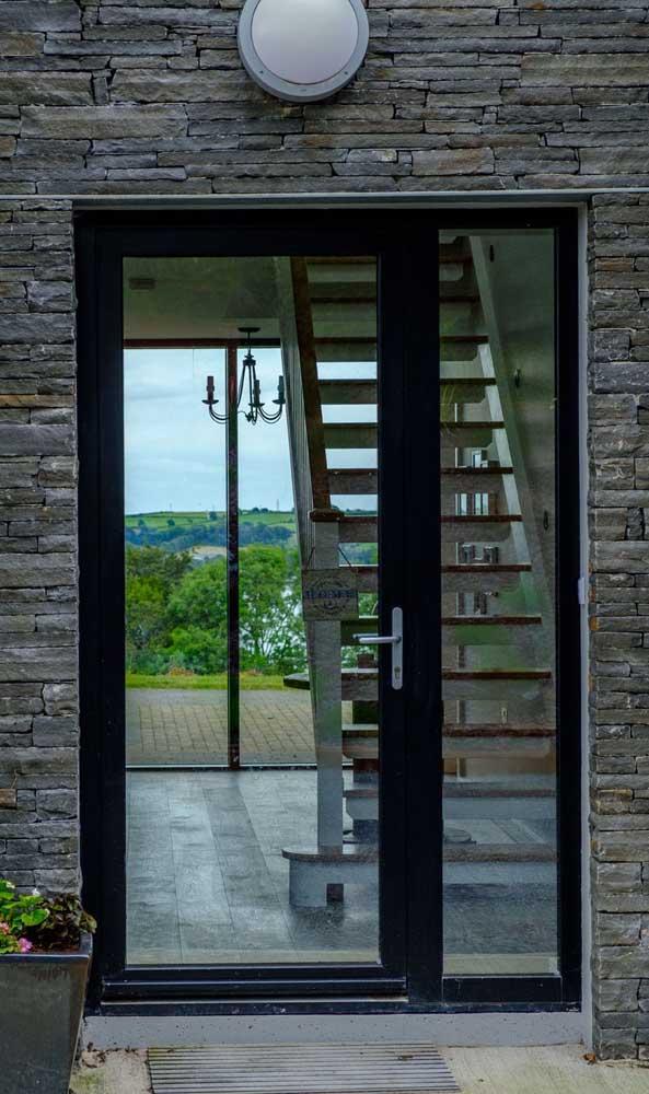 O vidro da porta de alumínio permite a contemplação da paisagem ao redor da casa