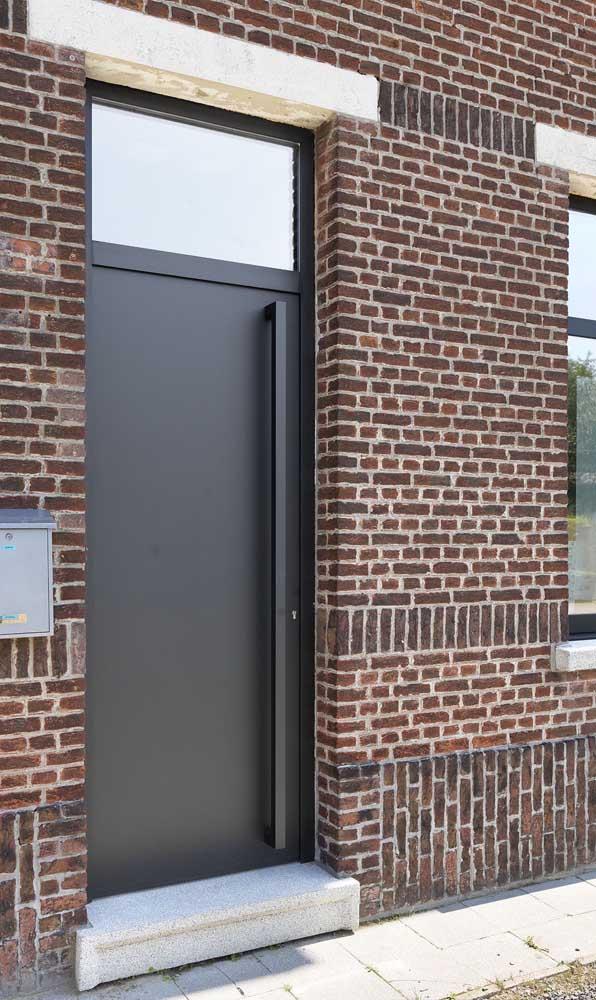 Porta de alumínio preto para a entrada da casa de tijolinhos