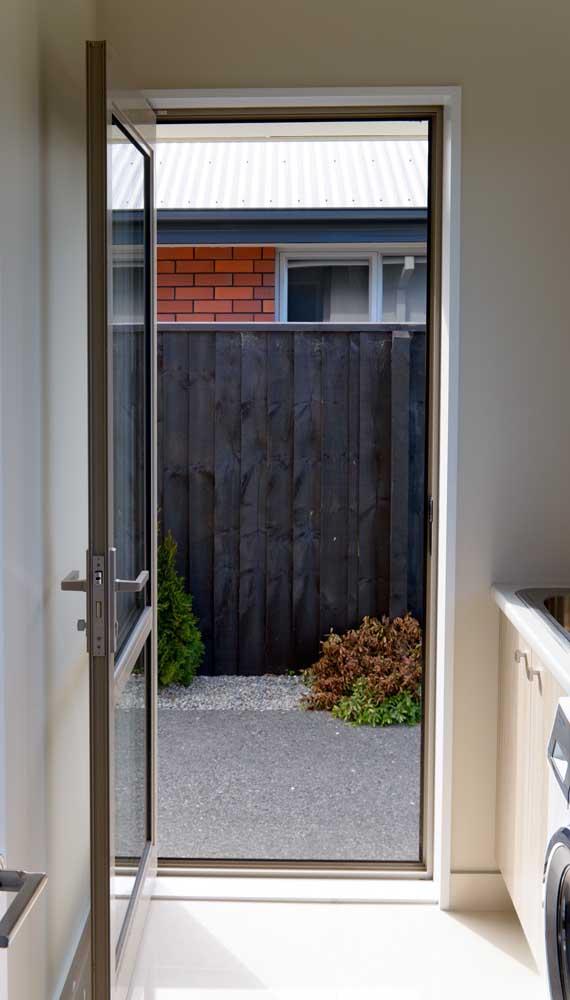 O quintal da casa pode ser acessado através da porta de alumínio com vidro