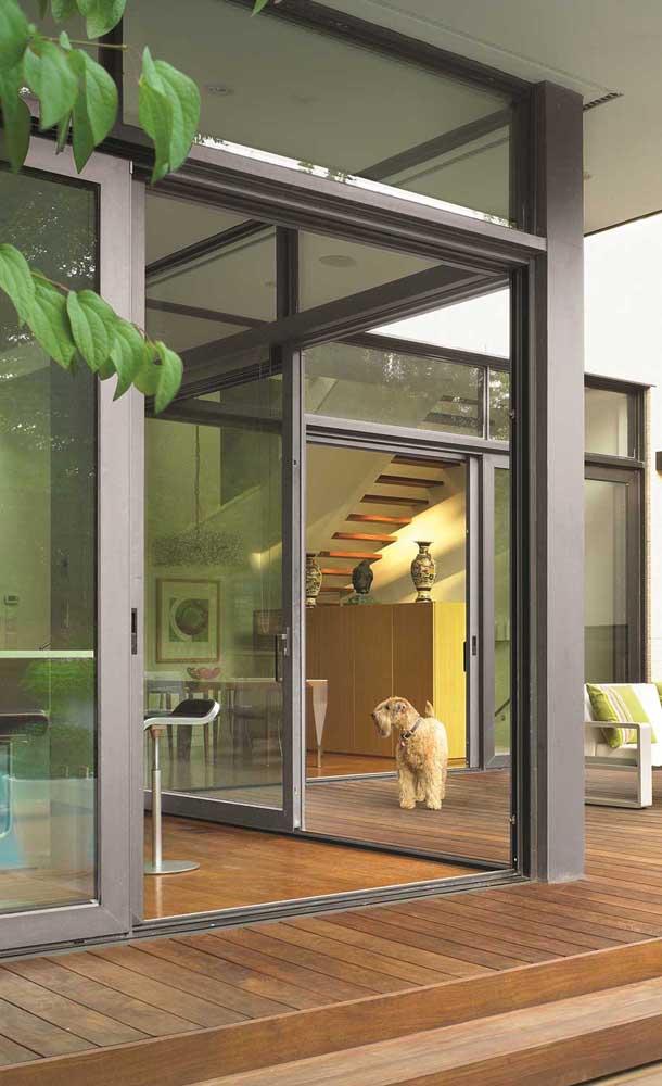 Nessa casa, as portas de alumínio fazem a transição entre o lado interno e externo