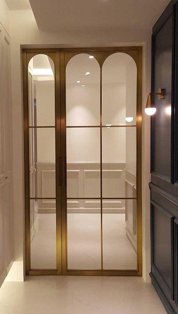 Pura elegância essa porta de alumínio dourada. Os vidros trazem ainda mais sofisticação ao projeto