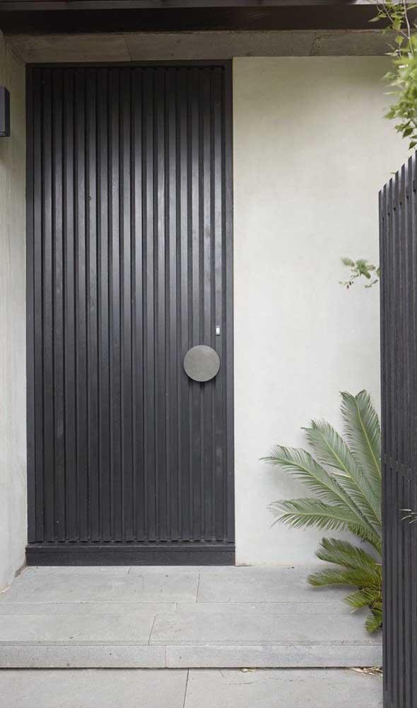 Aqui, a porta de alumínio preta ganhou frisos e um puxador super moderno