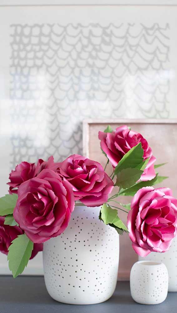 O vaso de cerâmica recebeu lindamente as rosas vermelhas de papel