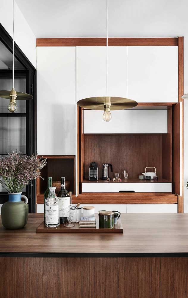 O balcão dessa cozinha americana traz um pequeno bar montado sobre a bandeja de madeira