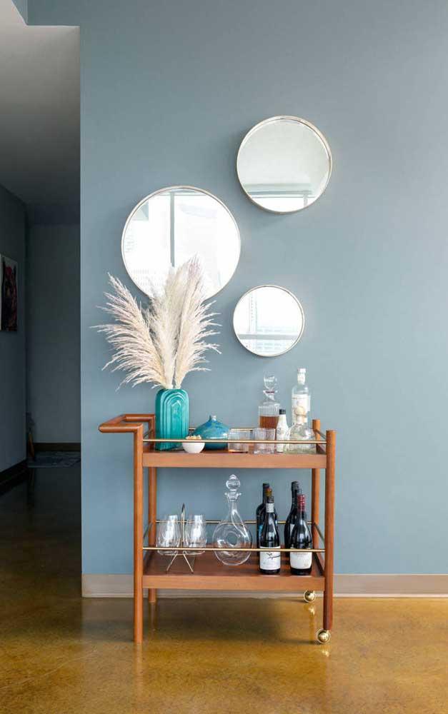 Carrinho bar com garrafas de vinho, algumas taças e um lindo trio de espelhos para arrematar a decoração