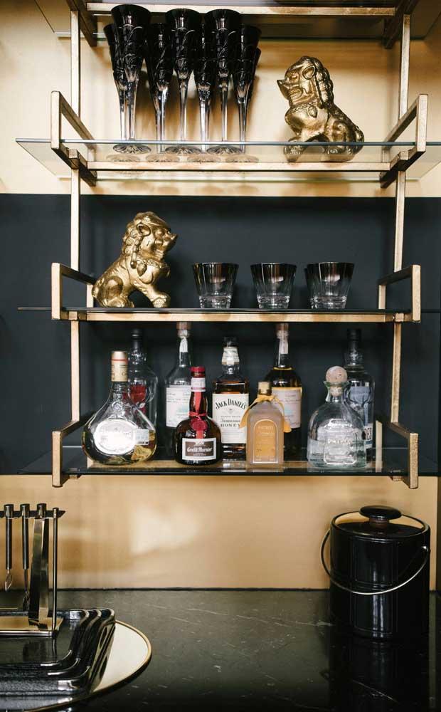 Prateleiras de vidro e detalhes dourados trazem glamour para esse mini bar em casa