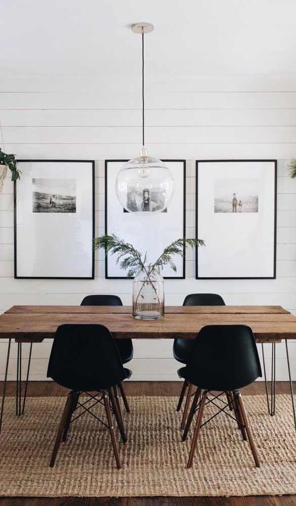 Moderna e minimalista, essa sala de jantar apostou na mesa de madeira de demolição acompanhada de cadeiras Eames Eiffel