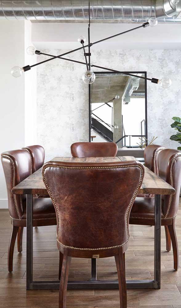 Cadeiras clássicas de couro em contraste com a mesa de madeira de demolição