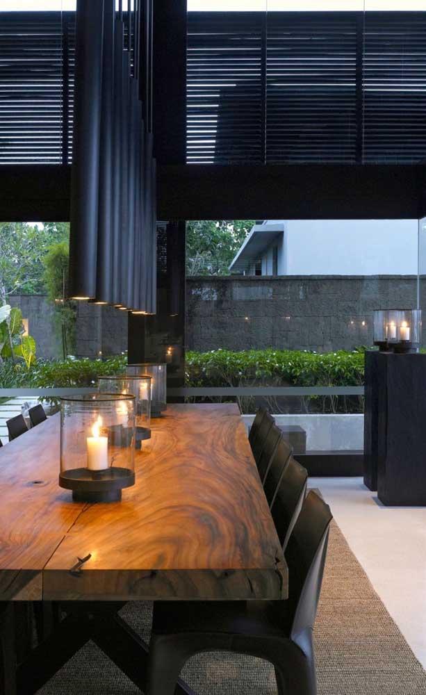 As velas trazem dramaticidade para essa mesa de madeira de demolição