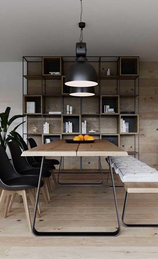 Nessa sala de jantar, a mesa de madeira de demolição harmoniza com o piso e o painel aos fundos, ambos também de madeira