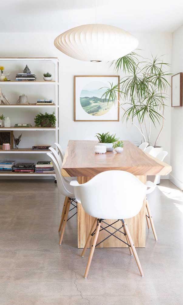 A luminária gigante ajuda a destacar e valorizar a mesa de madeira de demolição