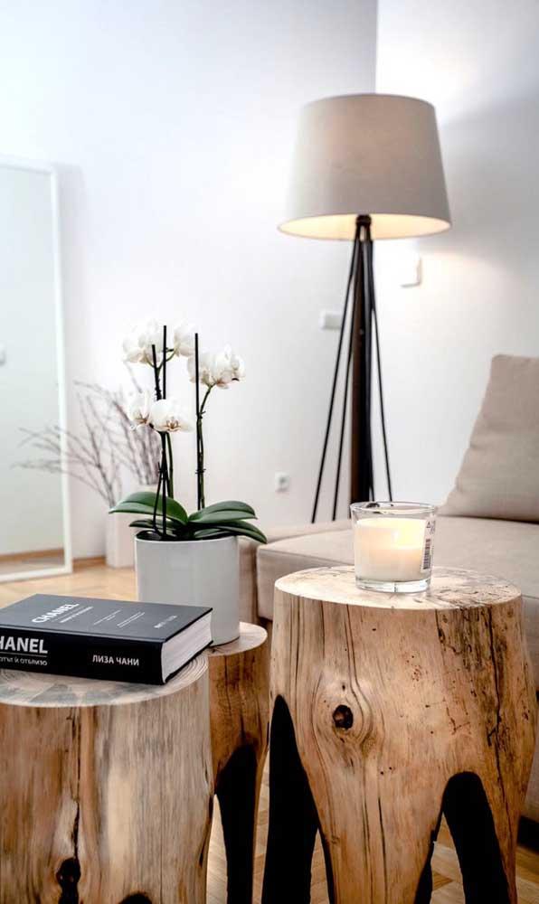 Três bancos de madeira de demolição servindo como mesa de centro na sala de estar