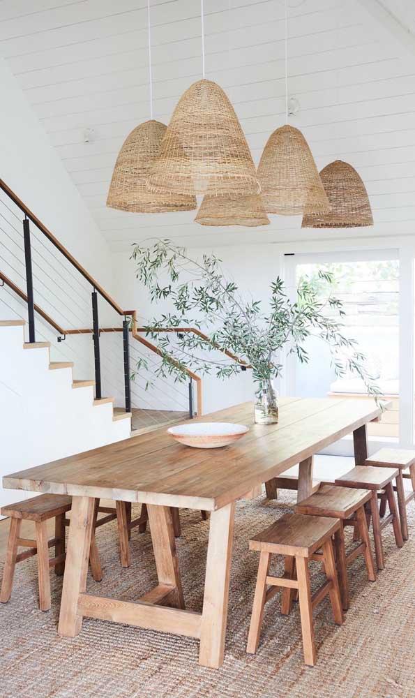 O clima praiano ficou garantido nessa sala de jantar com a mesa de madeira de demolição, o tapete de fibra e as luminárias de palha
