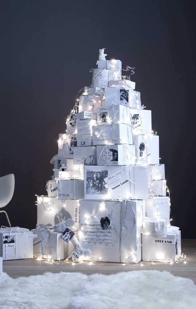 Pilha de presentes em formato de árvore de natal finalizada pelas luzes de pisca pisca