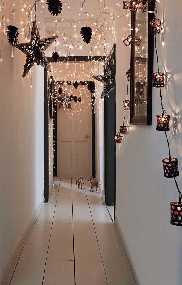 Que lindo esse corredor todo iluminado! Estrelas e pinhas completam a decor
