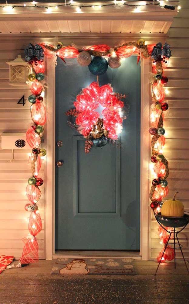 Fachada decorada com enfeites vermelhos e luzes de natal brancas