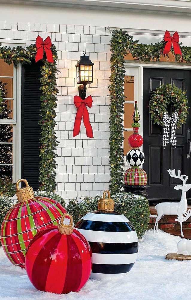 Fachada de casa decorada para o natal com bolas, renas e, é claro, muitas luzes