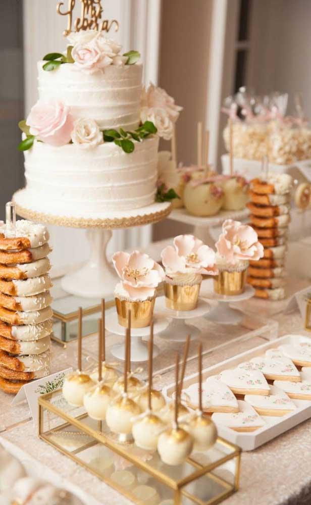 Mesa do bolo da festa de Bodas de Ouro. Rosas delicadas decoram os doces