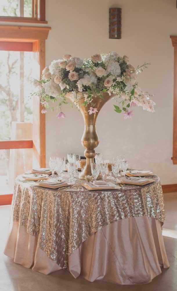 O vaso dourado cheio de flores é o destaque dessa linda mesa posta para festa de bodas de ouro
