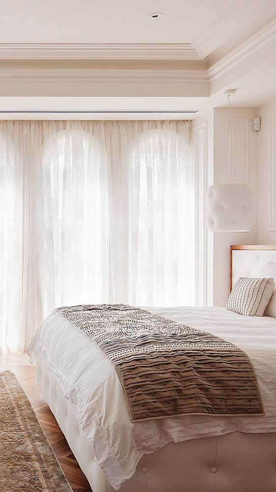 Repare na luz aconchegante que entra no quarto do casal através da cortina de renda