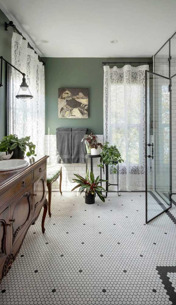 Esse banheiro amplo apostou em cortinas de renda longa para as duas janelas