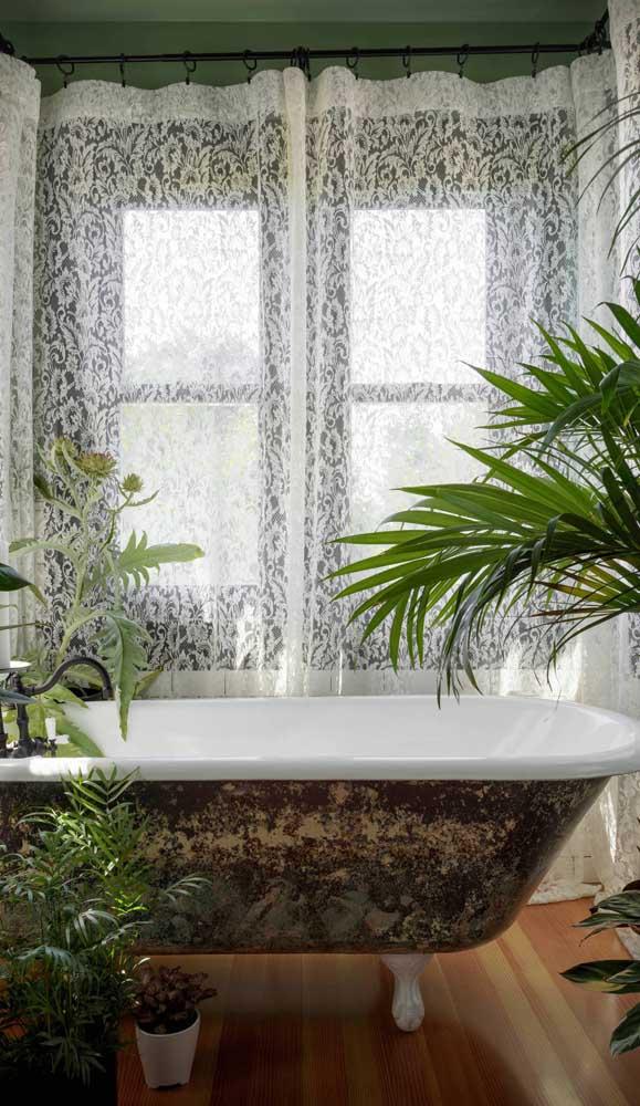 Aqui, a cortina de renda traz privacidade para o banho de banheira