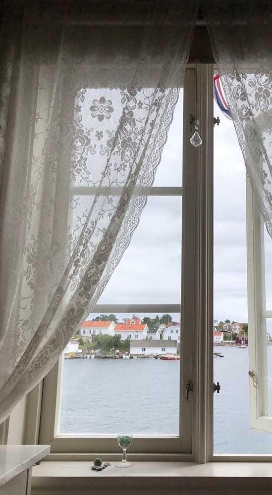 A janela com vista para o lago exibe uma cortina de renda floral
