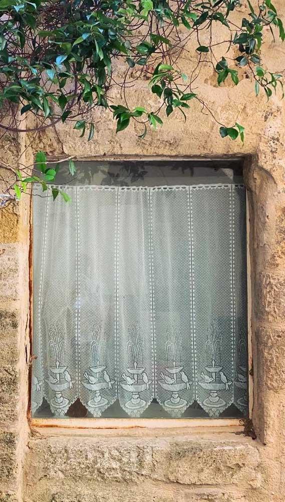 Passarinhos decoram essa pequena cortina de renda exposta na janela rústica