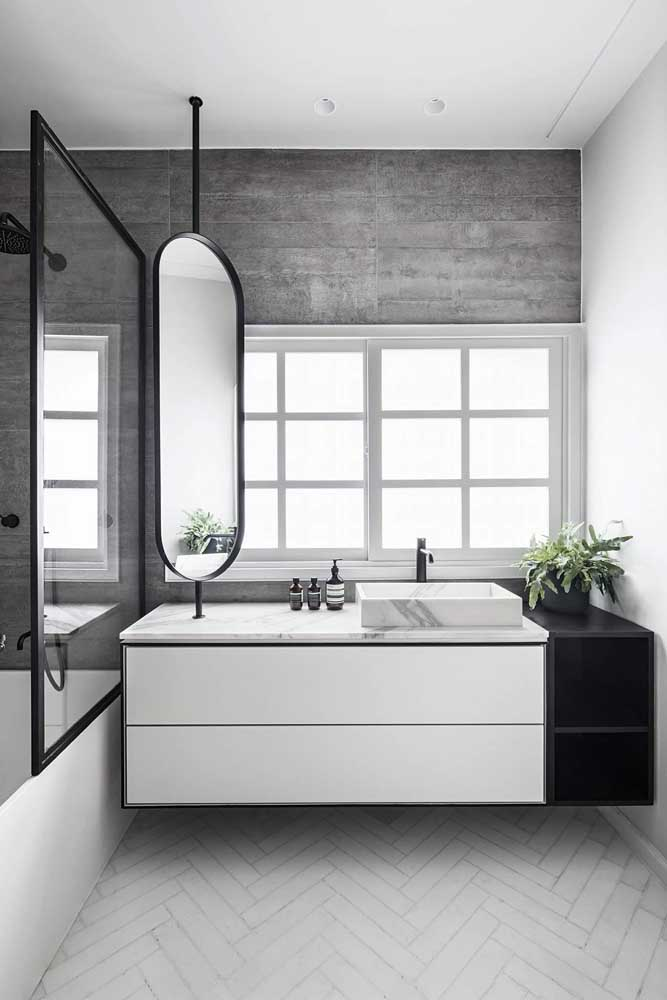 Para esse banheiro moderno a escolha foi por uma janela grande de correr instalada junto a bancada da pia