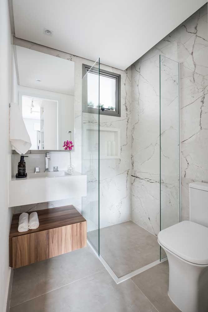Banheiro pequeno com janela basculante instalada na parte superior da área do banho