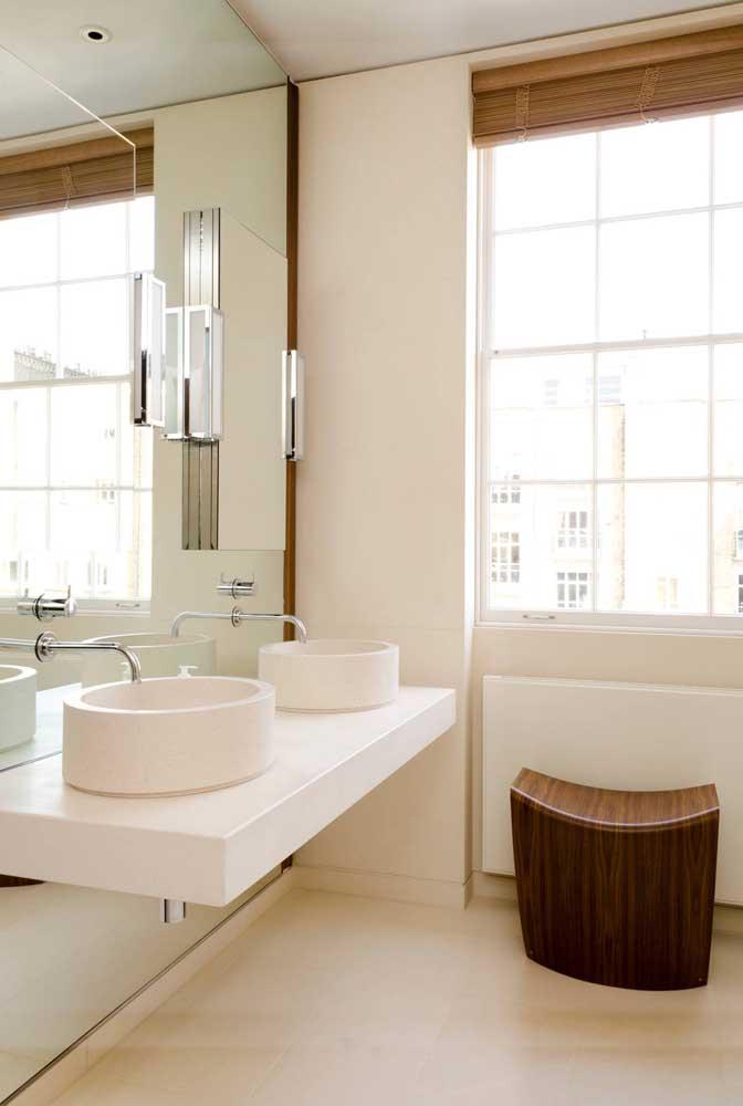 A ampla janela de alumínio branco ganhou uma persiana de bambu para assegurar a privacidade dos moradores